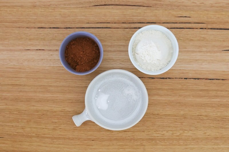 A bowl of plain flour, a bowl of cocoa powder and a sprinkle of bi-carbonate soda and salt.
