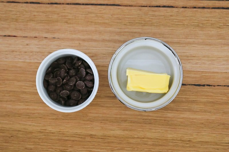 A bowl with butter and a bowl with dark chocolate melts