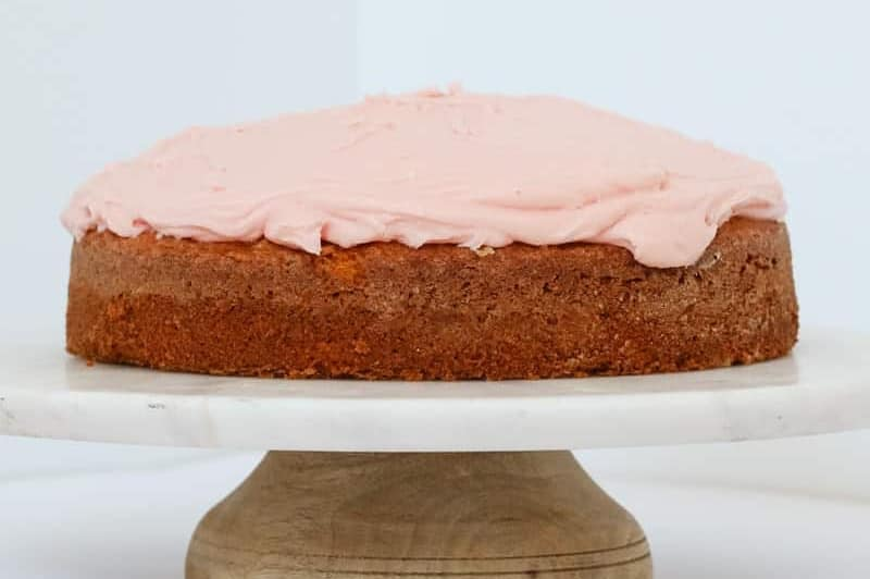A butter cake with pink frosting sitting on a white cake stand
