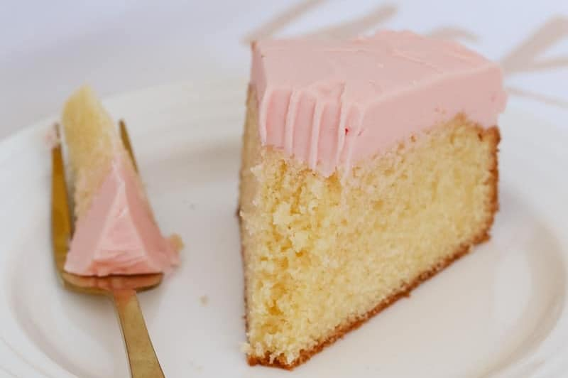 A serve of a butter cake topped with pink frosting with a forkful removed and sitting beside