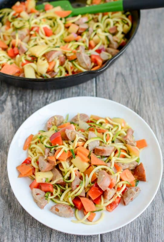 Chicken and sausage skillet with zoodles being served onto a white plate.