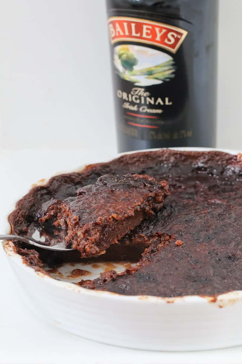 A cake scoop lifting a piece of chocolate pudding from a round dish with Baileys irish cream in the background.