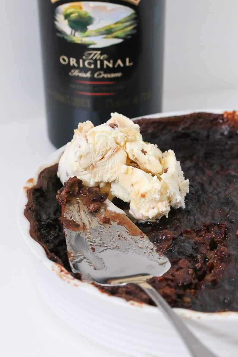 A bottle of Baileys behind a baking dish of chocolate pudding behind dished up.