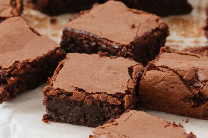 A close up of squares of a dense and moist brownie slice