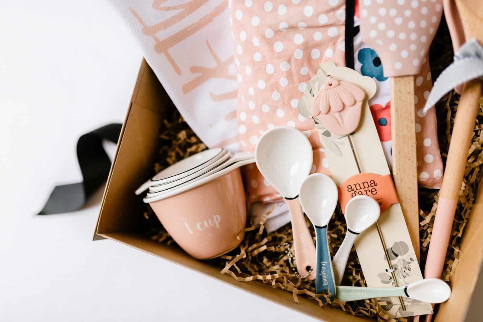 A hamper of baking goodies - pink enamel measuring cups, measuring spoons, tea towels and cake testers