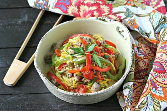 Sausage and peppers over zucchini noodles in a bowl with chopsticks.