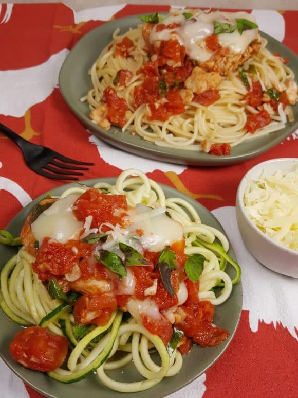 Picture is of two plates on a red and white tablecloth. On one plate is a mound of cooked spaghetti topped with chopped tomato and baked chicken pieces with melted cheese and chopped basil. On the other plate is the same except the spaghetti is actually zucchini noodles.