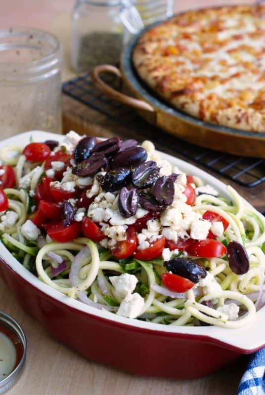Picture is of a kitchen bench, in the background is a wooden block with a cooked cheese pizza surrounded by jars with chopped herbs in them. In the foreground is a red casserole dish filled with zucchini noodles topped with chopped tomatoes, olives and crumbled feta - a healthy zoodles recipe.