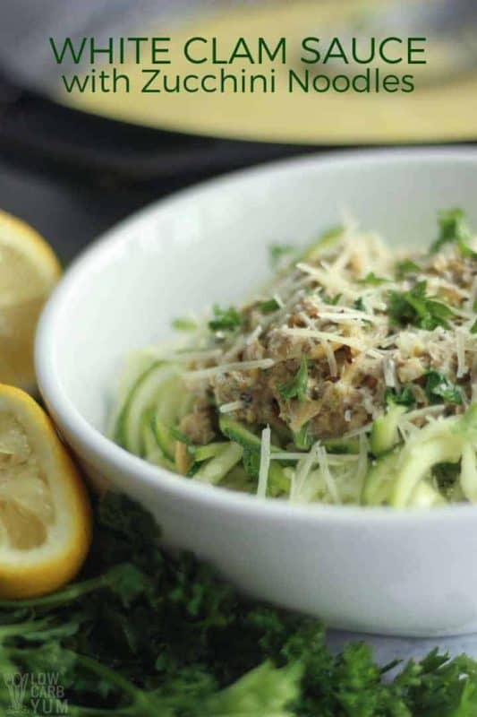 Picture is of a white bowl filled with green spiralled zucchini topped with minced meat, parsley and parmesan cheese. Surrounding the bowl is lemon slices and herbs.