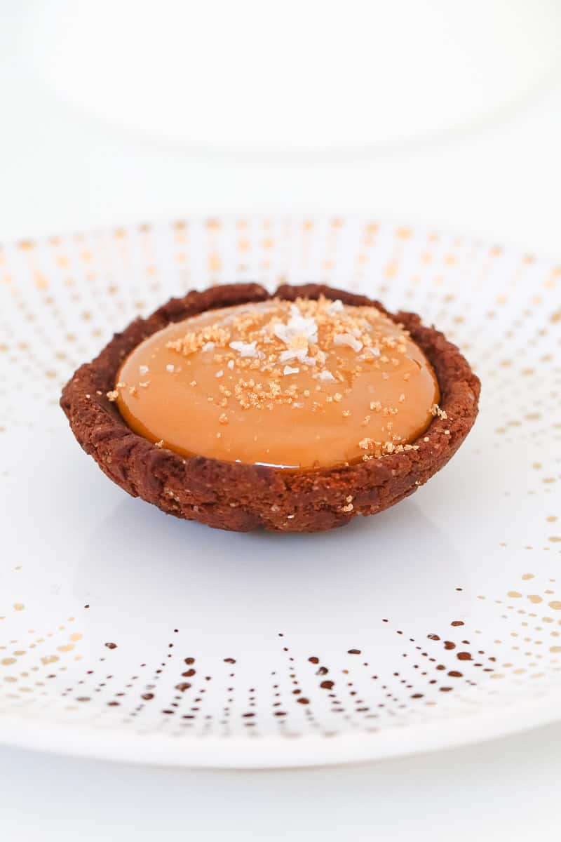 A round chocolate biscuit with caramel filling and sea salt on top.