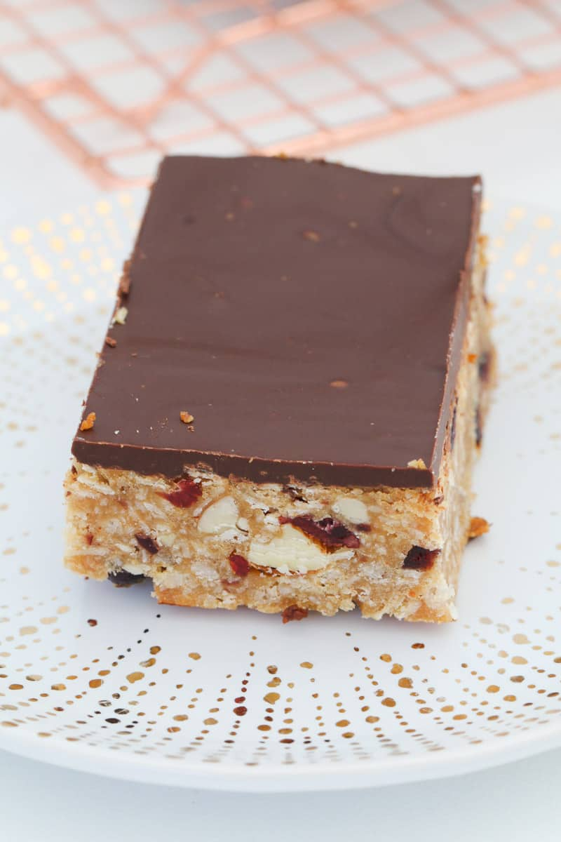 A piece of muesli bar with dark chocolate topping.