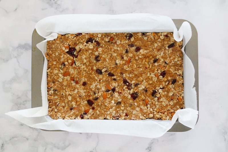 Granola bars mixture being pressed into a baking tin.