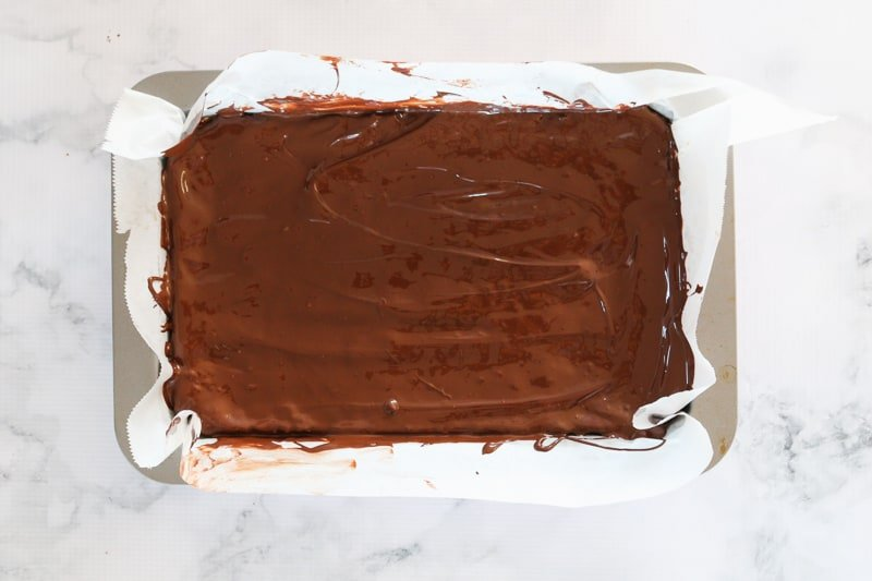 Melted dark chocolate being spread over the top of a slice.