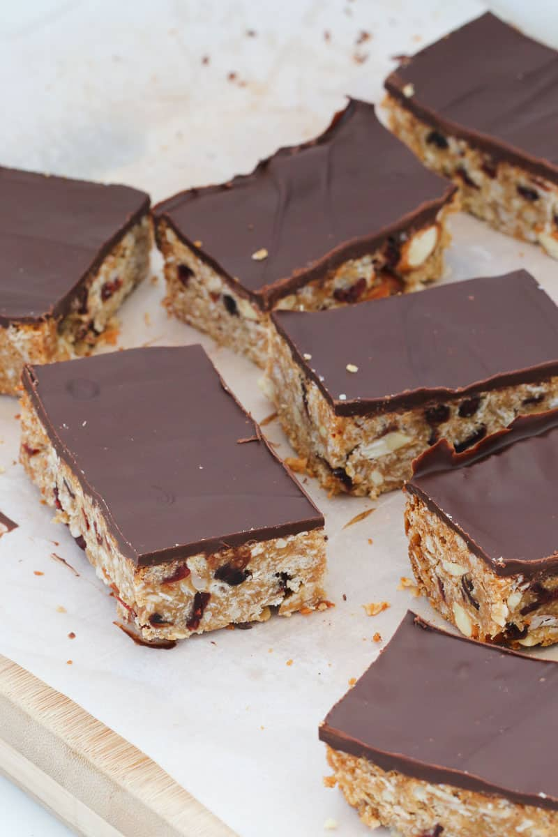 Chocolate topped, cranberry and almond muesli bars on a piece of baking paper.