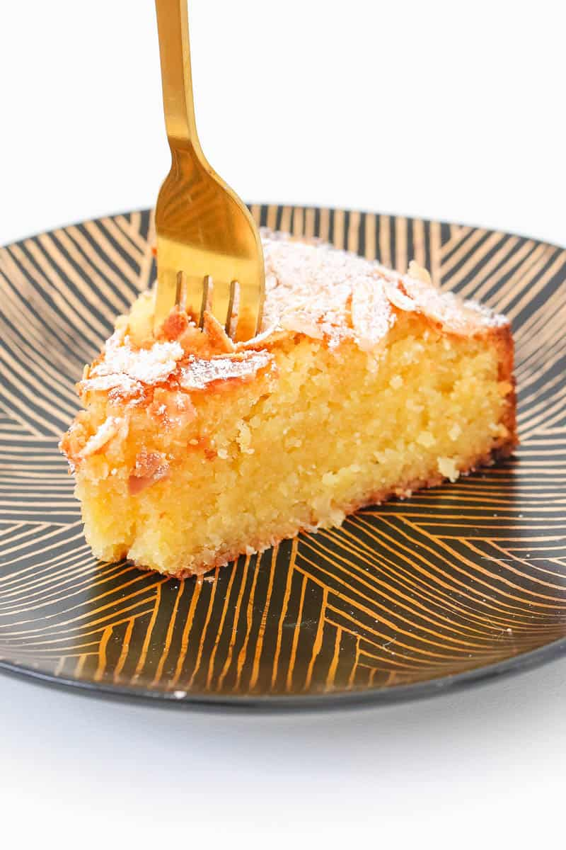 A fork being inserted into a piece of yellow cake with icing sugar on top.