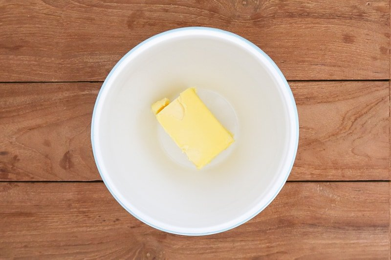 A piece of butter sitting in a white bowl.