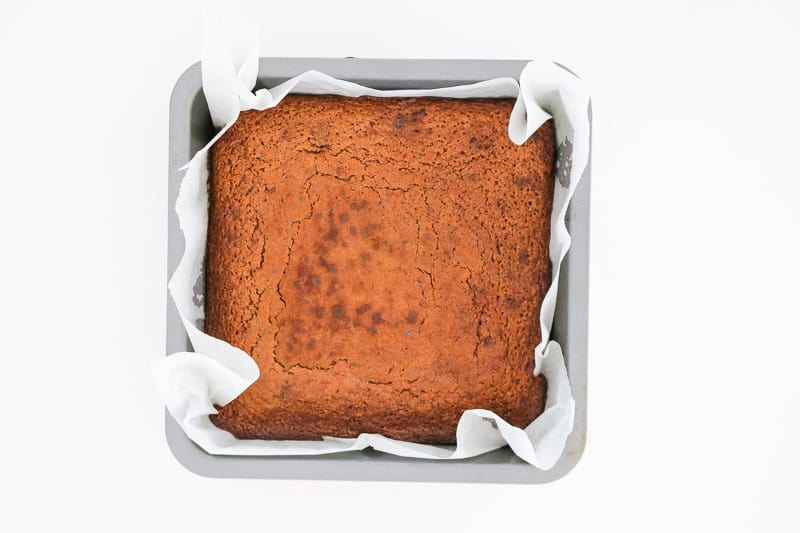 A chocolate slice in a baking tin just out of the oven.