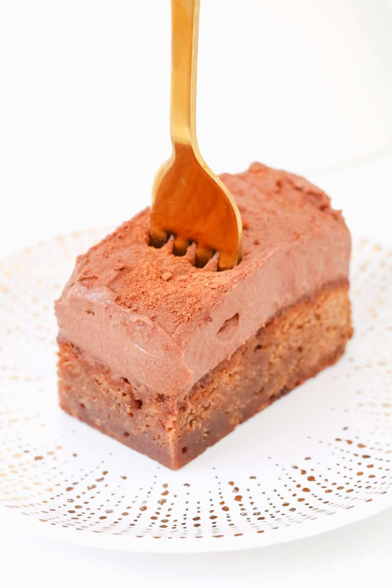 A gold fork being pressed into a piece of chocolate mousse dessert cake.