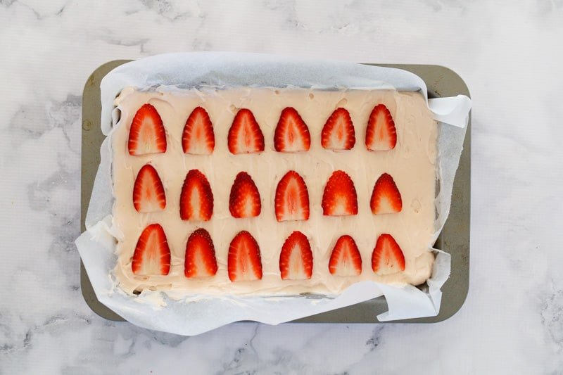 Fresh and sliced strawberries on top of a cheesecake slice.