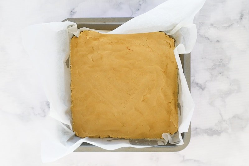 A shortbread base in a square baking tin.