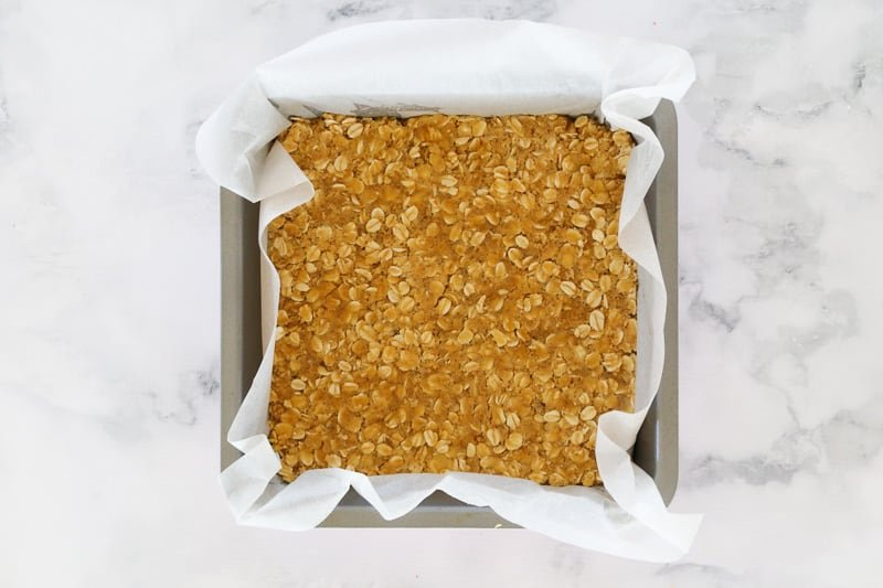 Oat crumble pressed firmly into a baking tin.