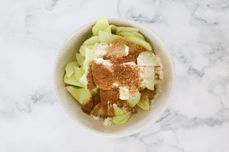 Apple slices in a bowl with sugar, flour, cinnamon and nutmeg.