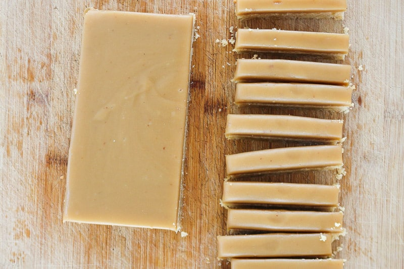 A layer of caramel being cut into bars on a chopping board.