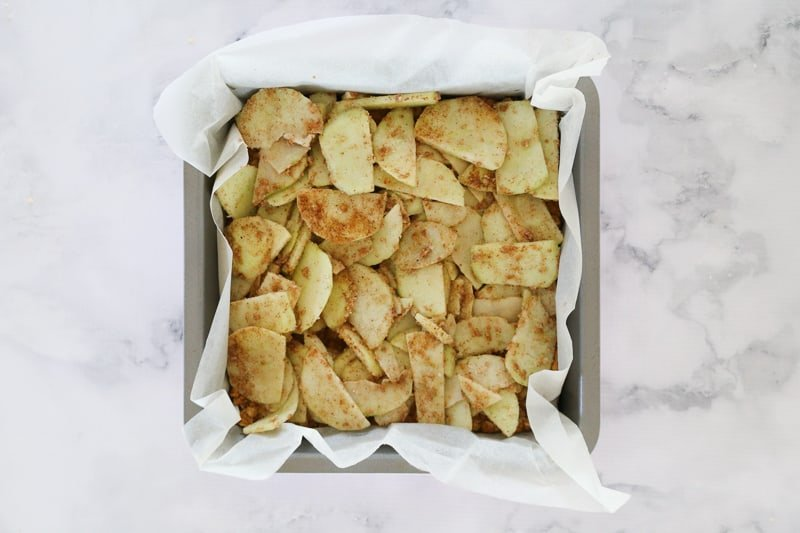 Apple slices with cinnamon and nutmeg in a square baking tin.