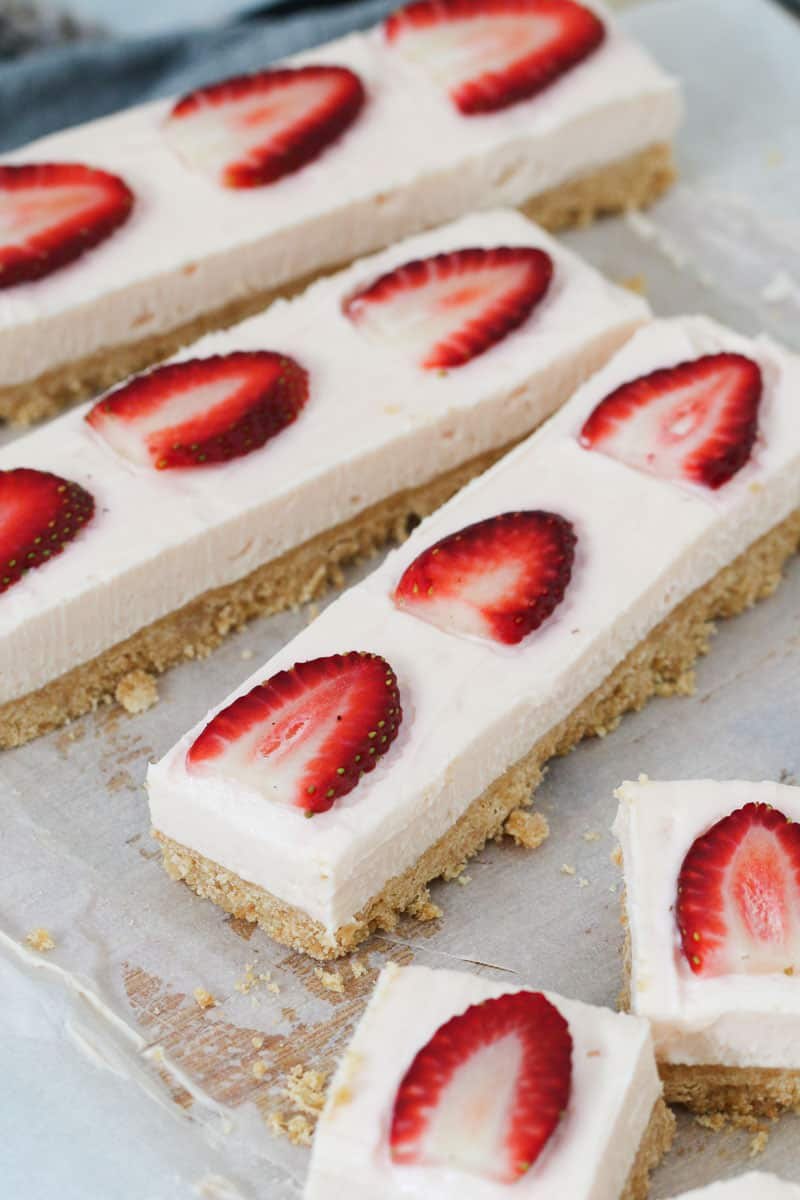 Strawberry cheesecake slice being sliced into squares on a chopping board.