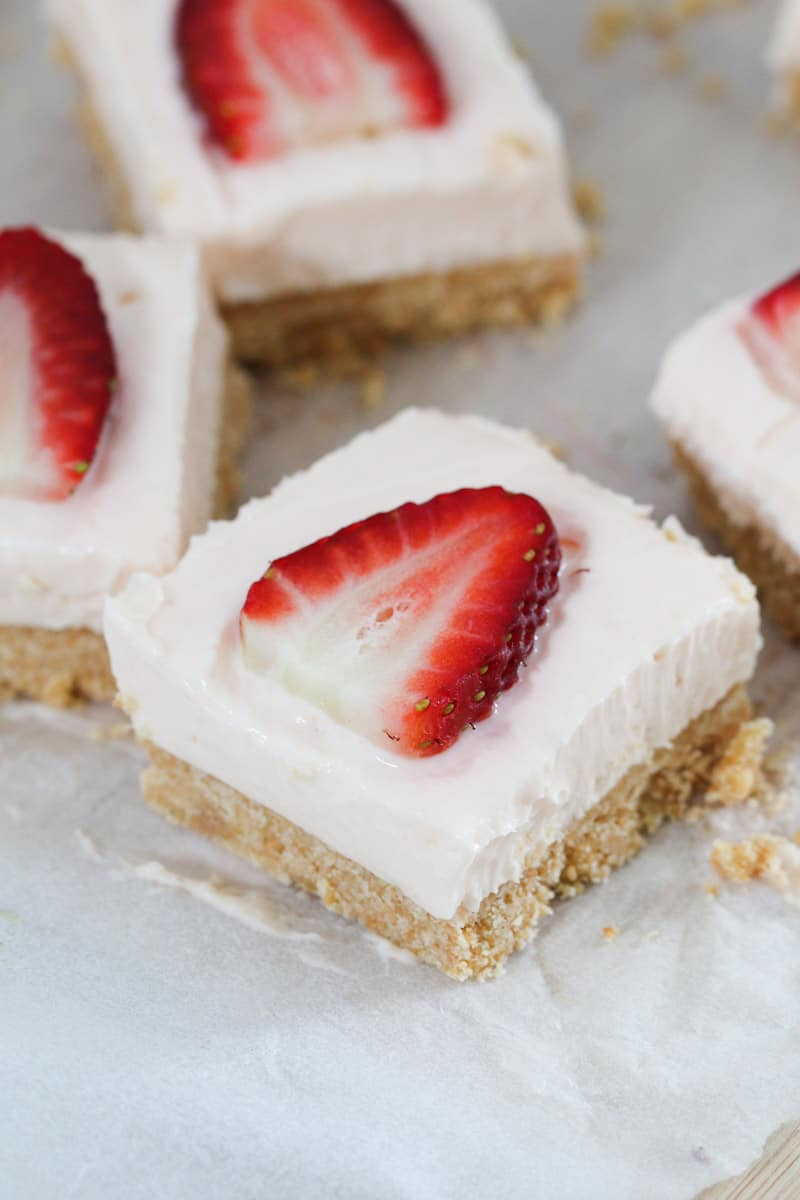 Squares of strawberry cheesecake bars with sliced fresh strawberries on top.