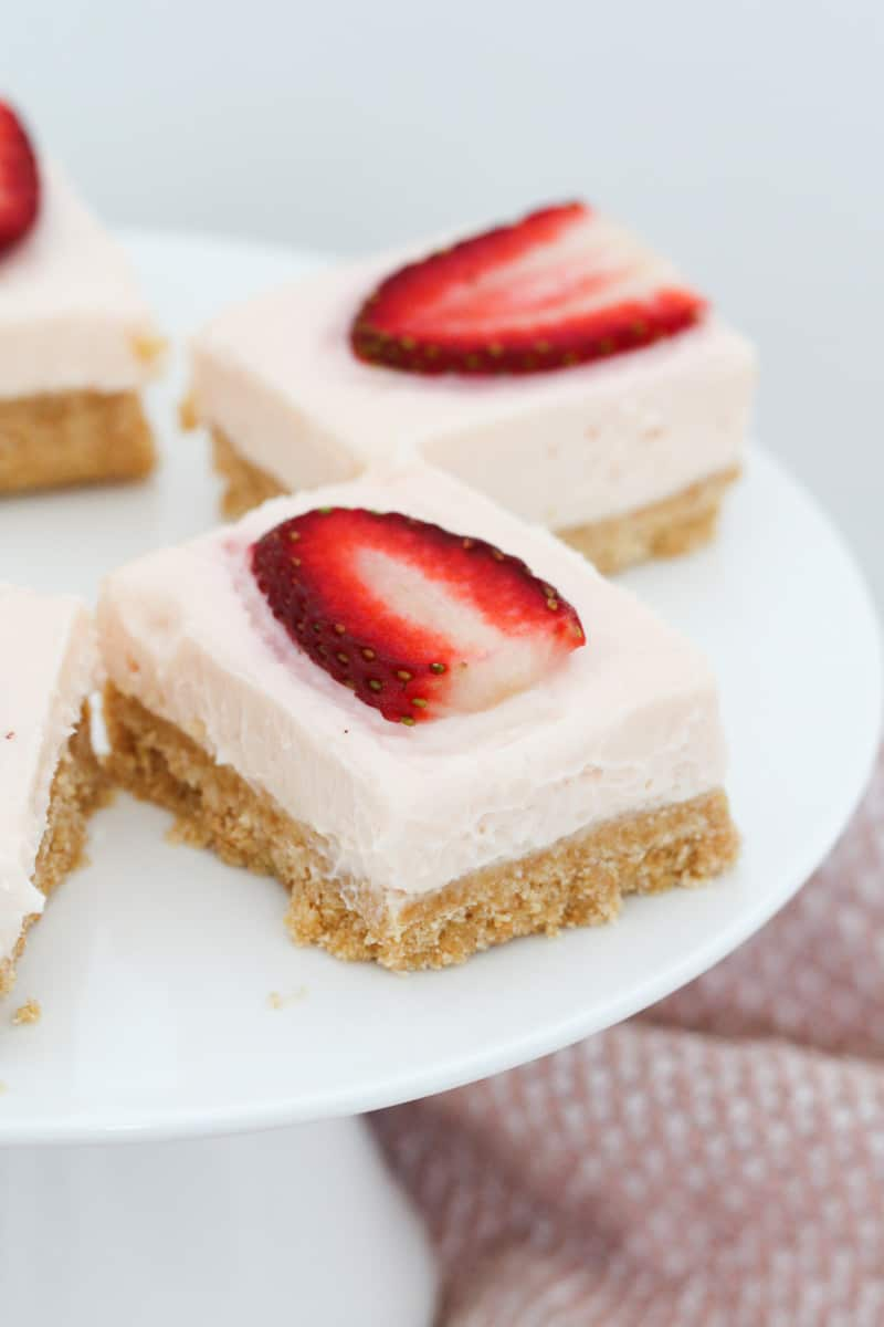 Fresh strawberries on top of pieces of cheesecake slice.