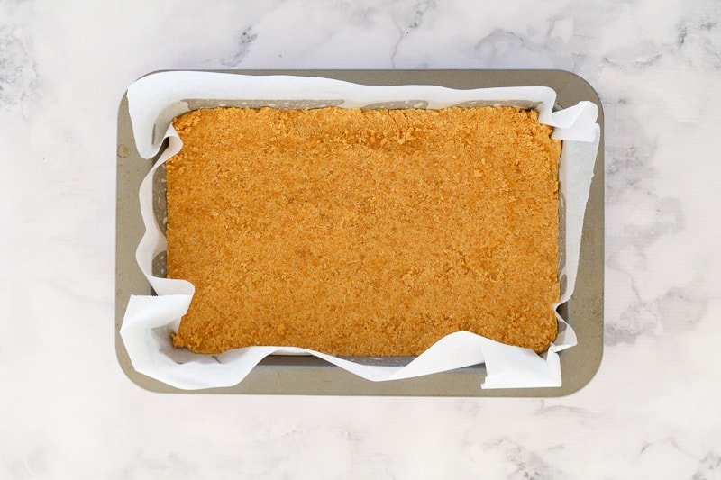 Biscuit crumbs pressed firmly into the base of a lined slice tin.