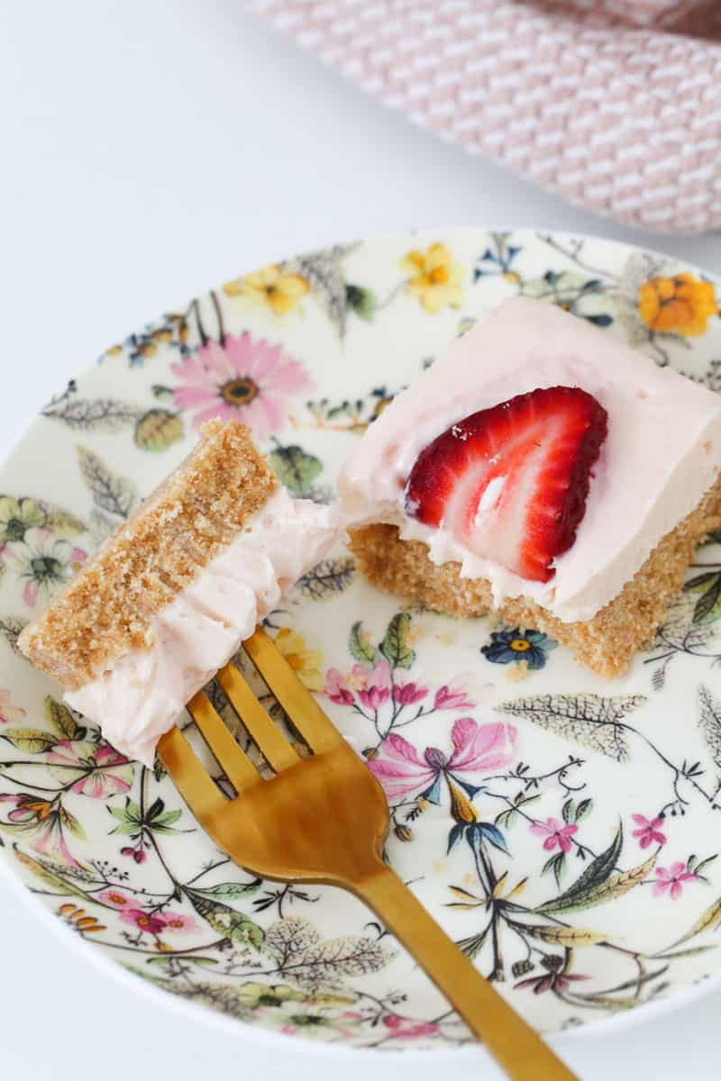 A gold fork with a piece of strawberry cheesecake on it, on a pretty floral plate