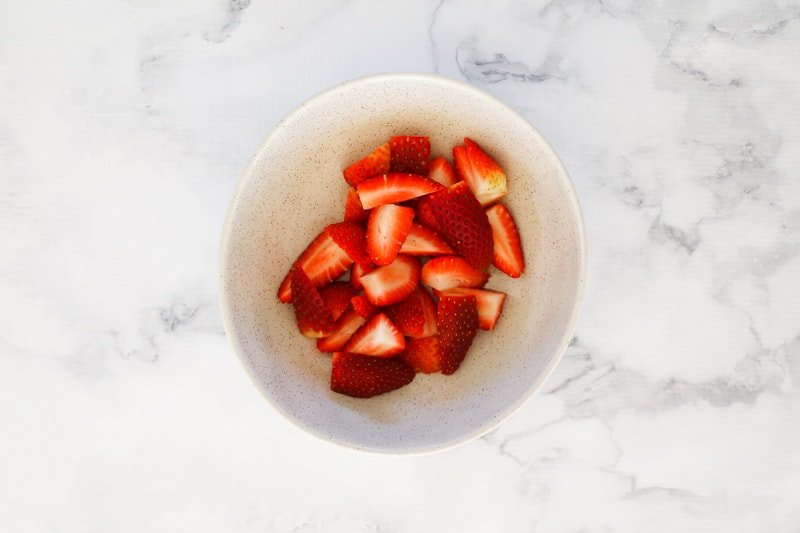 Cut up strawberries in a bowl.