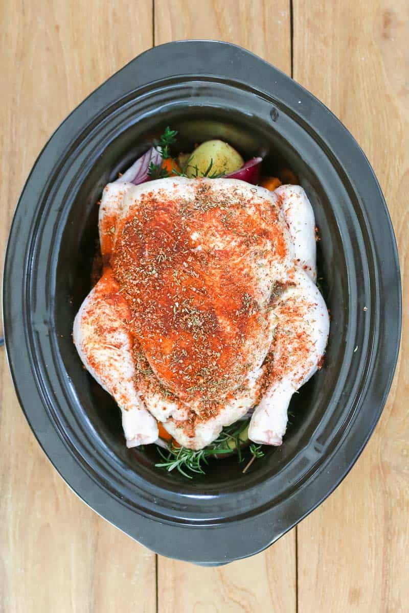 Seasoning added to a whole chicken in a slow cooker.