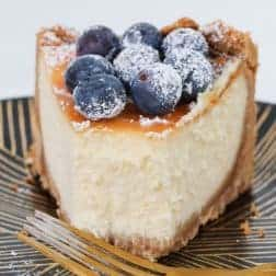 A slice of baked cheesecake decorated with blueberries and sprinkled with icing sugar on a plate.