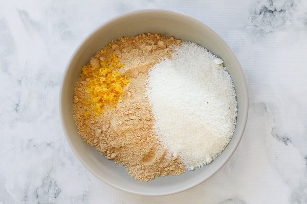 Coconut, cookie crumbs and lemon zest in a bowl.