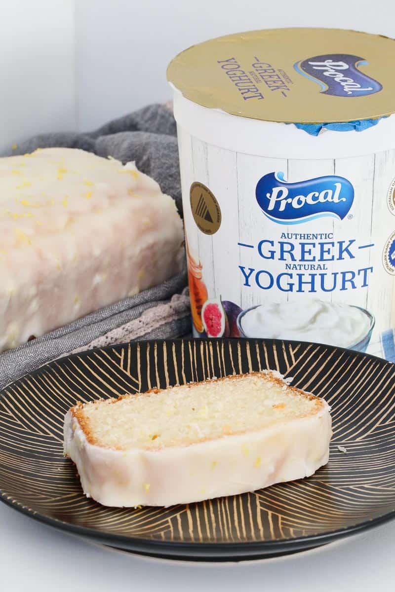 A tub of greek yoghurt behind a slice of lemon yoghurt loaf.