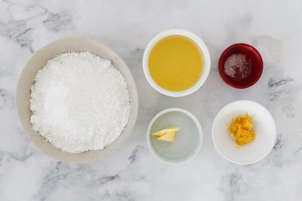 The ingredients for an easy lemon icing glaze - icing sugar, butter, lemon juice, salt and lemon zest.