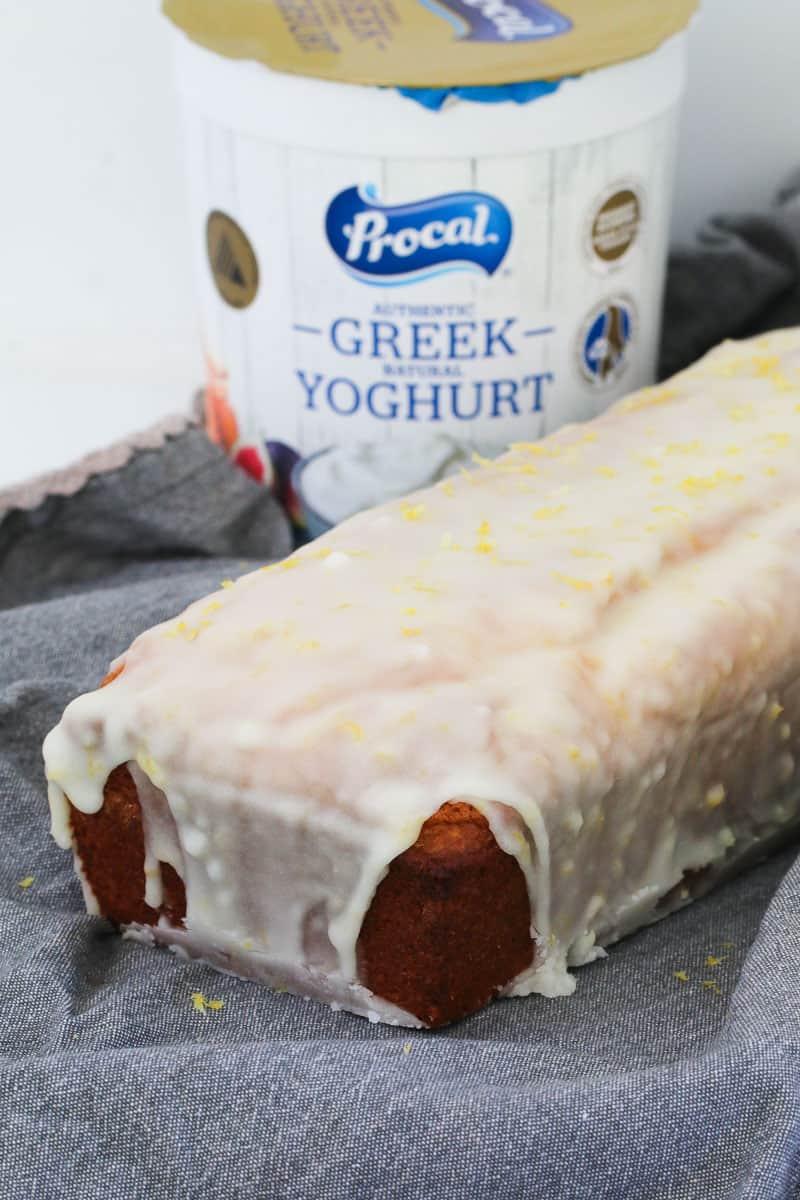 A tub of greek yoghurt behind a lemon glazed loaf.