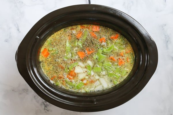Chicken stock, herbs and vegetables in a slow cooker.