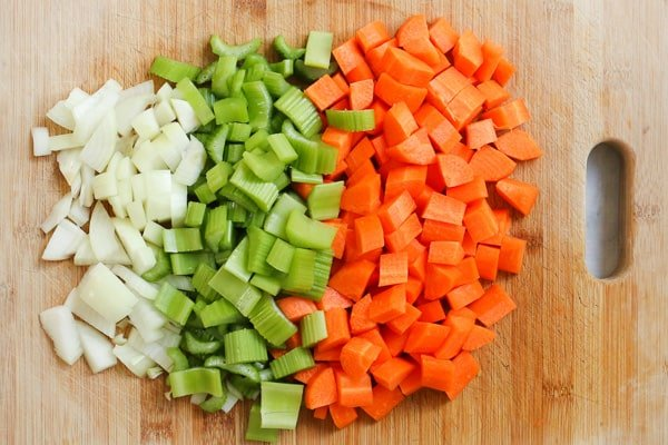 Chopped carrots, celery and onion on a chopping board.