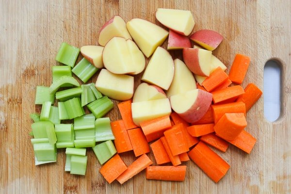 Chunks of potatoes, carrots and celery on a chopping board.