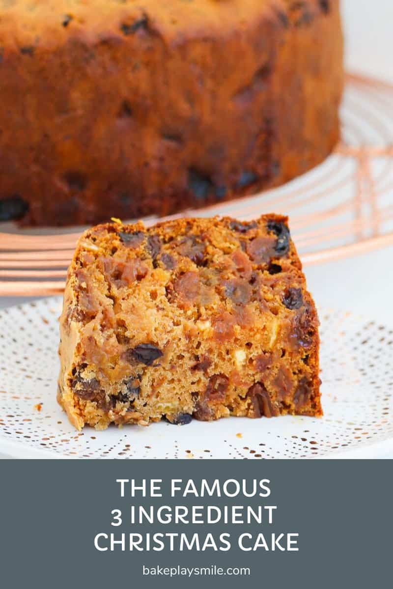A piece of Christmas fruit cake on a plate, with the rest of the cake b=in the background