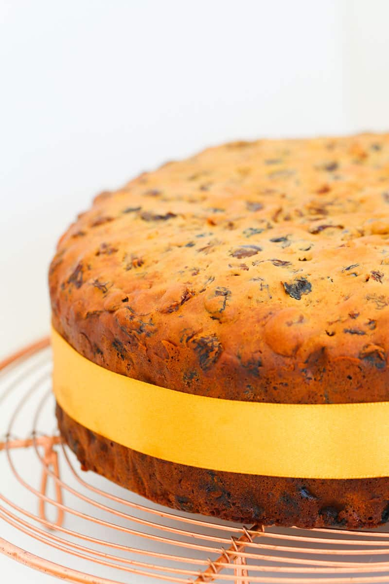 A golden fruit cake with a gold ribbon around it sitting on a copper wire tray.