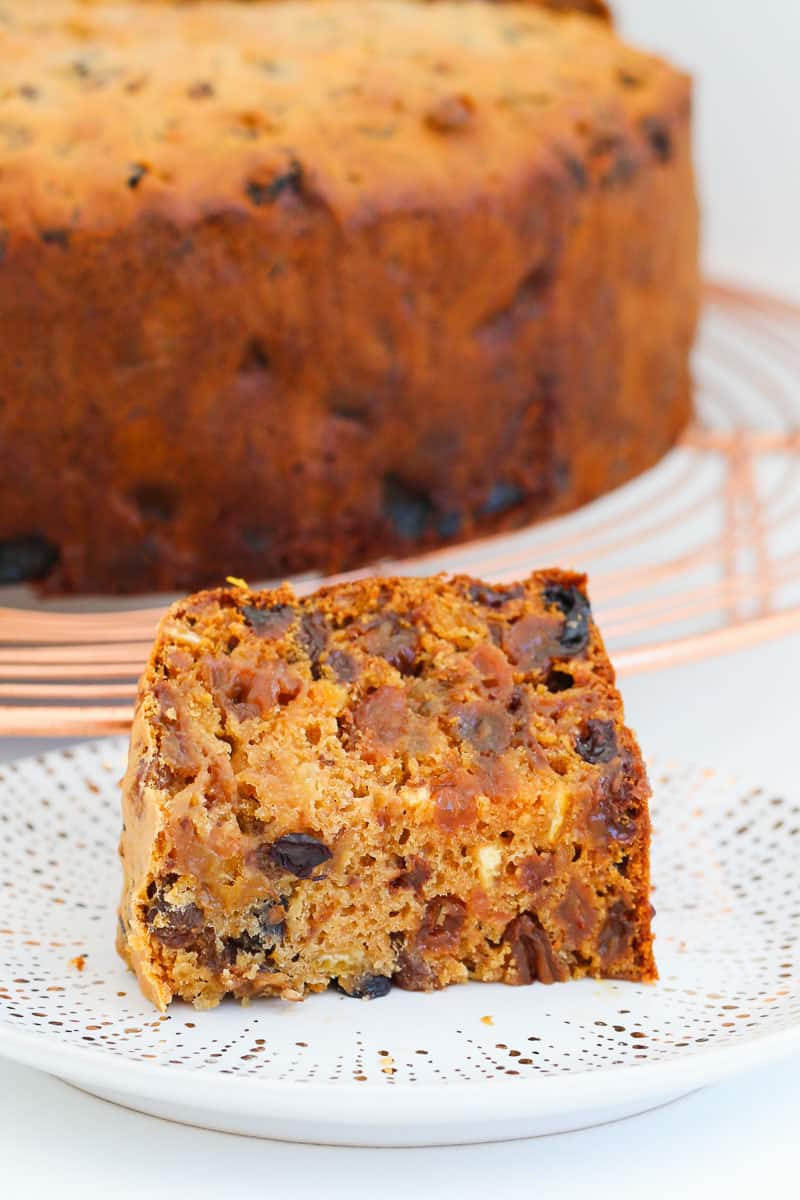 A piece of fruit cake with the whole cake in the background.
