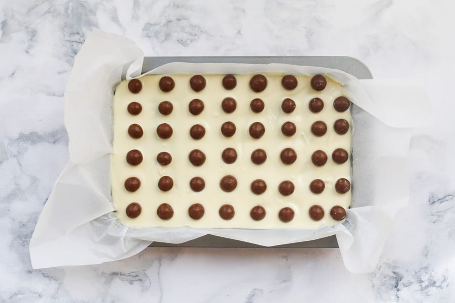 Maltesers on top of white chocolate in a slice tin.