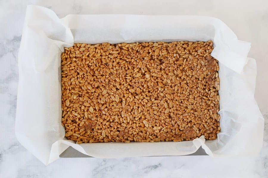 Chocolate rice bubble slice mixture pressed into a baking paper lined rectangular tin.