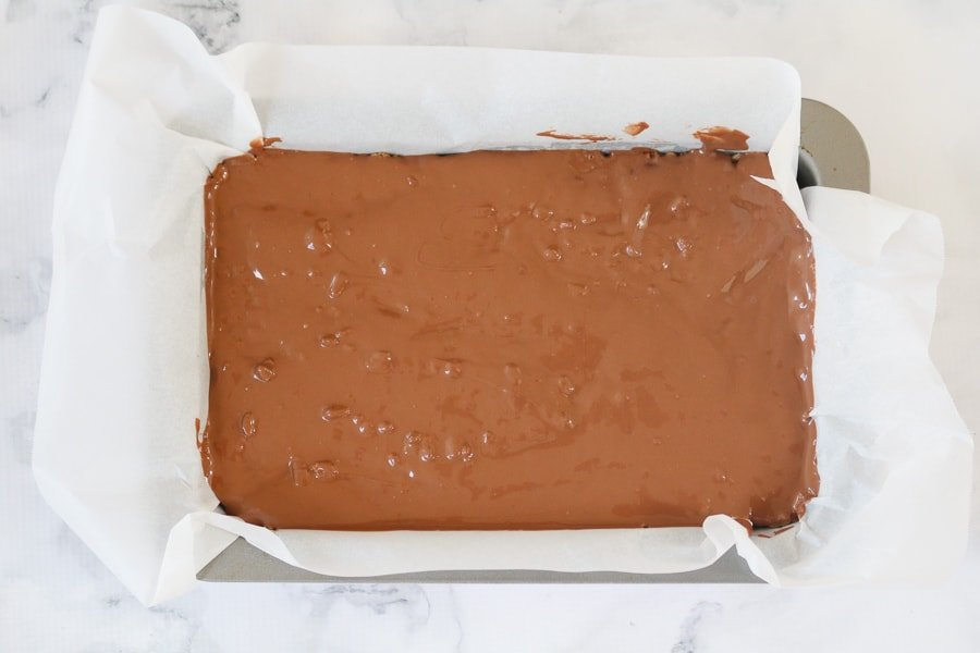 Melted chocolate spread over a no-bake chocolate, caramel and rice bubble slice in a baking tin.
