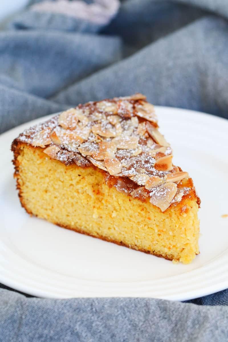 A slice of orange almond cake on a white plate.